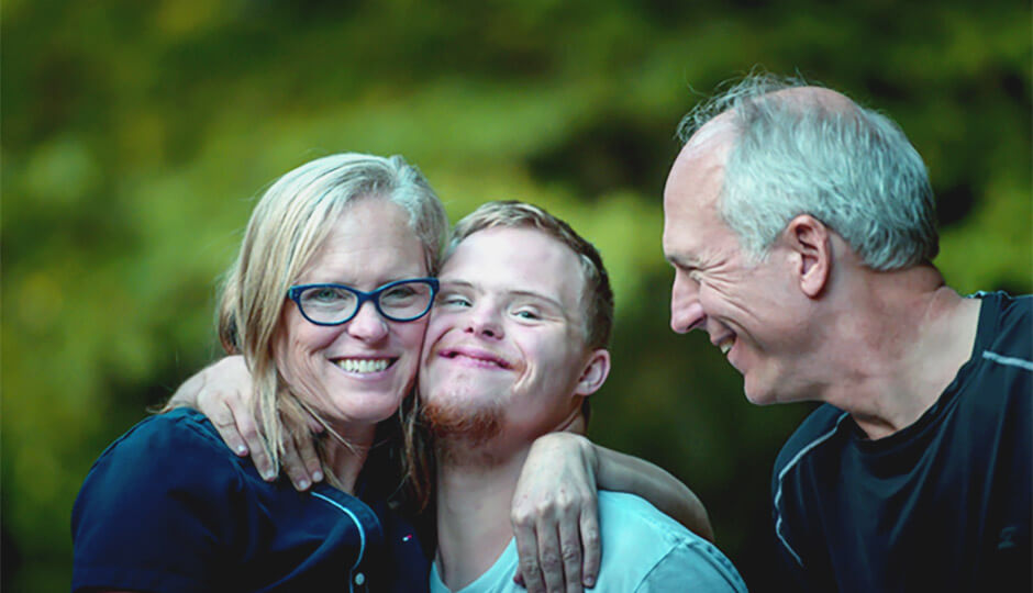 A man and woman enjoy time outside with their son who is living with Down's syndrome