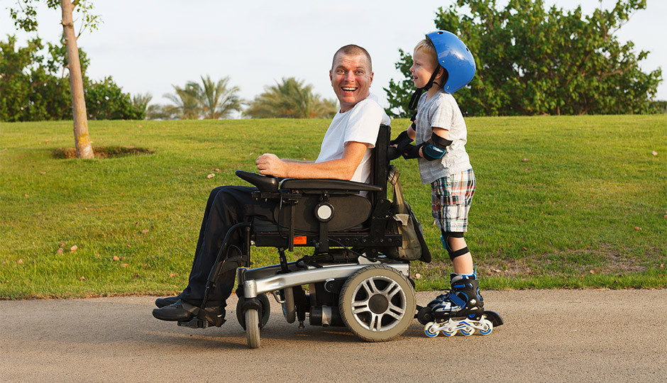 A child on roller blades with a blue helmet pushes his father in a wheelchair as they enjoy the outdoors together